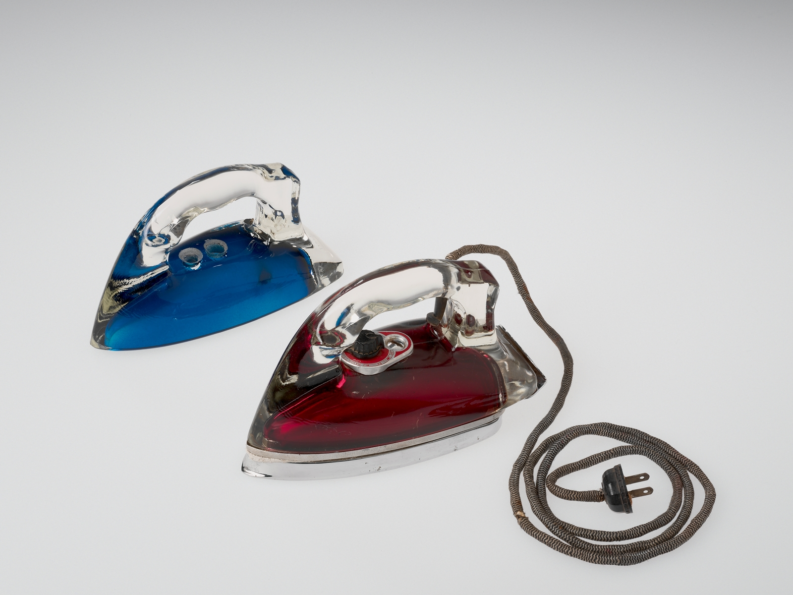 Silver Streak Iron Insert (blue) and Silver Streak Electric Iron (red), United States, Corning, NY, Corning Glass Works; Saunders Machine and Tool Corporation, made in 1946; designed in 1943; Blue: H: 11.7 cm, W: 21.6 cm, D: 9.6 cm; Red: H: 12.5 cm, W: 22
